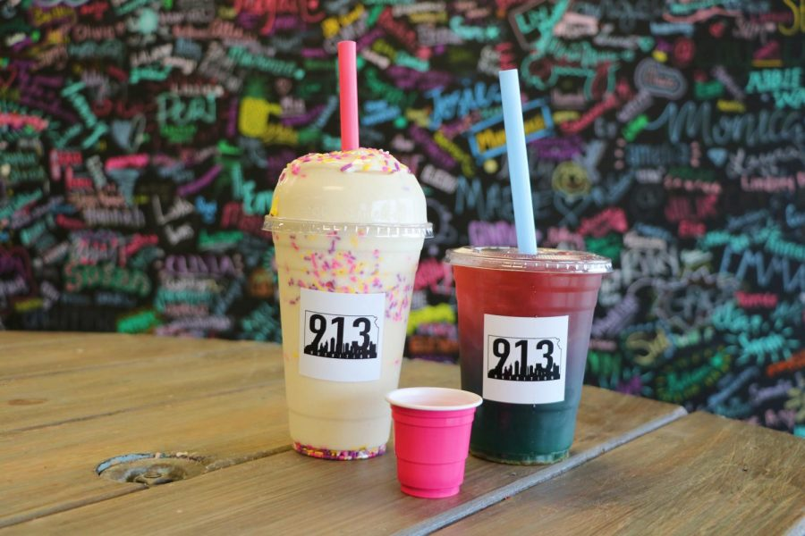 'The Mermaid' tea, 'Birthday Cake' nutrition shake, and an aloe shot from 913 Nutrition are shown in front of the colorful wall full of customer signatures.
