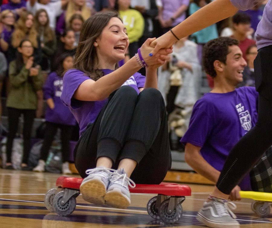 Junior Katelyn Foster rides on a scooter during the class games at the homecoming assembly, on Oct. 11.