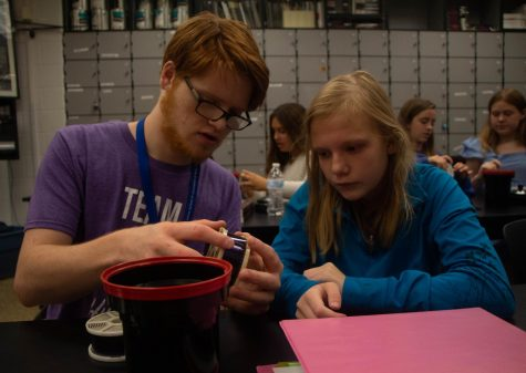 """Matthew Maher helps sophomore Ashleigh Eblen develop film in art teacher Melanie Mikel's photography class. """"The students are always so happy to be there. They don't judge anyone and they always come in with a smile on their face,"""" Maher said."""