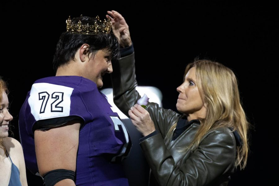 Amy Robinson places a crown on top of senior Danny Robinson as he is crowned homecoming king, on Oct. 11.