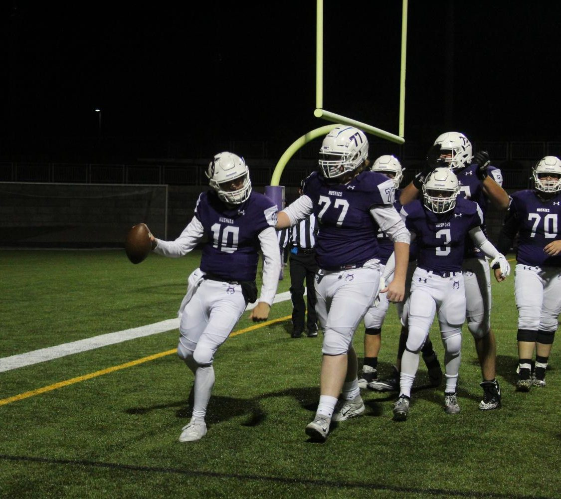 Sophomore quarterback Mikey Pauley celebrates a touchdown during the varsity football game, on Oct. 11.