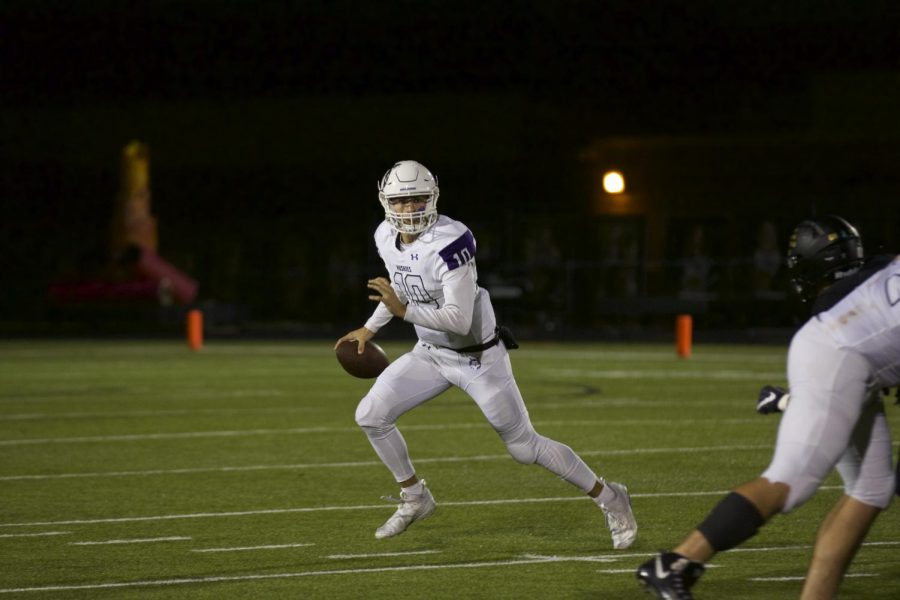 Sophomore quarterback Mikey Pauley escapes the pocket in a game against Blue Valley on Oct. 4.