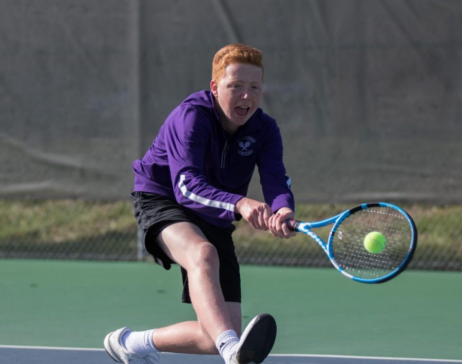 Sophomore Cooper Pennington hits a backhand during a match against Shawnee Mission South, Apr. 4.
