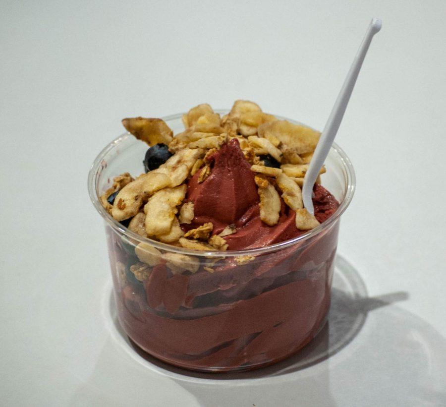 An acai bowl from Costco  topped with banana chips and blueberries is placed on a table.