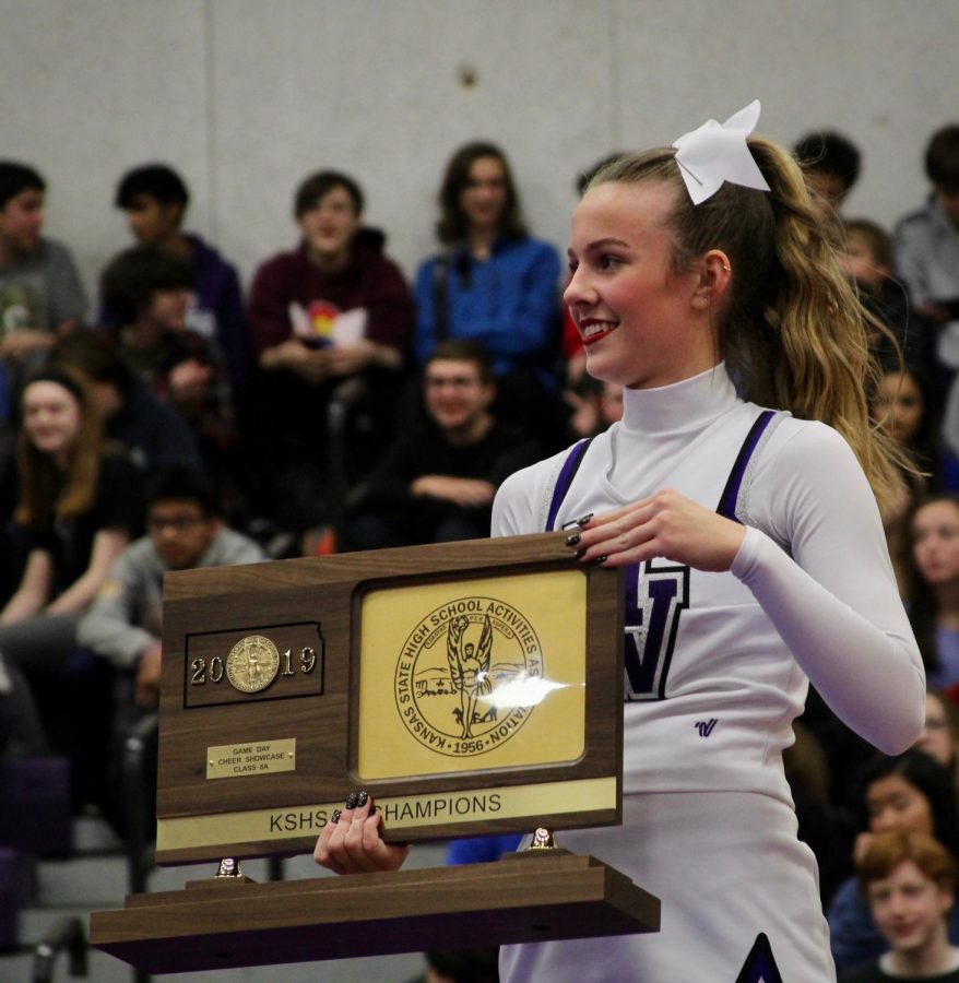 Senior Campbell Newby holds the state championship trophy before handing it to Dr. Pressly, on Dec. 2.