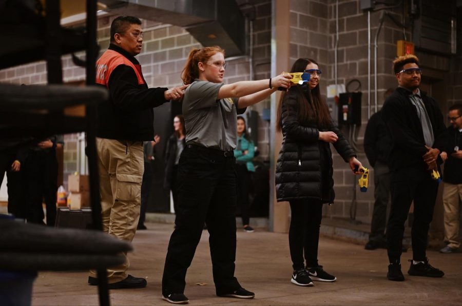 "Senior Taylor Crowell aims a stun gun at a dummy. ""My favorite part of Explorers is getting to meet all these new people from different schools, and getting to know the officers who volunteer their time. We have so much fun and it's nice to see more into the daily life of a police officer, and you just get a whole new perspective and newfound appreciation. So meeting new people and gaining these connections is my favorite part,"" Crowell said."