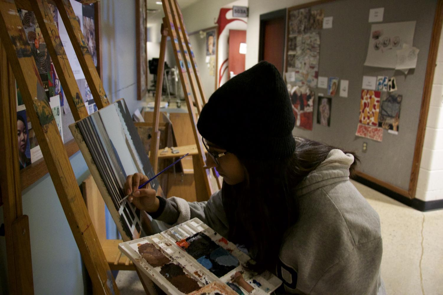 Junior Alina Mahli paints a picture in the art hallway, on Nov. 16.