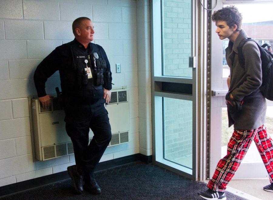 An OP Police Officer stands inside the senior doorways Thursday morning.