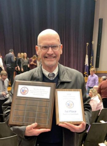 Ken Thomas, the advisor of We the People, poses with the state championship plaque.