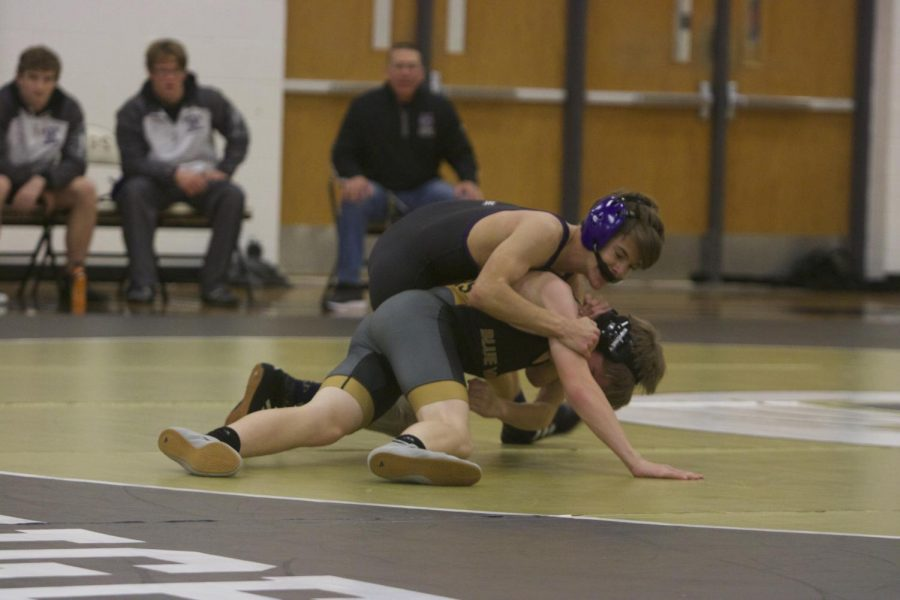 Freshman+Thomas+Peterson+looks+to+win+his+match+against+his+opponent+in+the+dual+against+Blue+Valley.