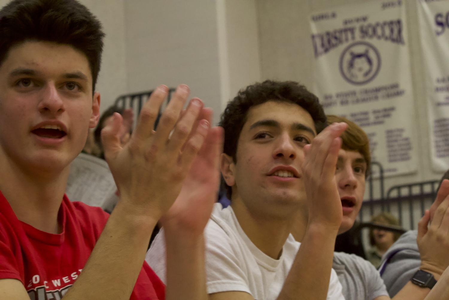 Sophomores Brain Nicholson, Yousif Radhi and Aidan Barnes cheer together at a home JV basketball game.