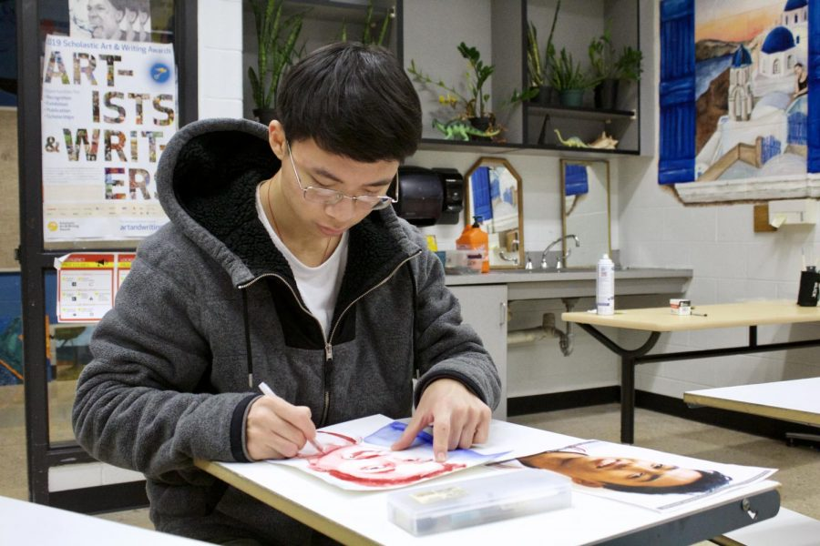 Senior John Chen works on a portrait drawing for the Memory Project.
