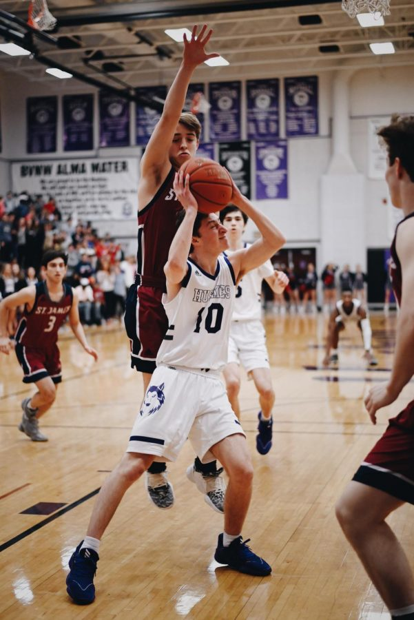 Senior Luke Blau (10) puts up a contested layup during his first varsity start of his career during senior night.