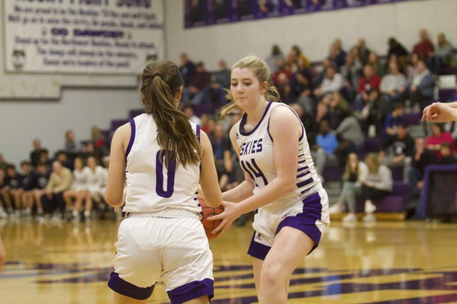 Senior Camryn Threinen (44) hands the ball off to sophomore Hayley Numrich (0).