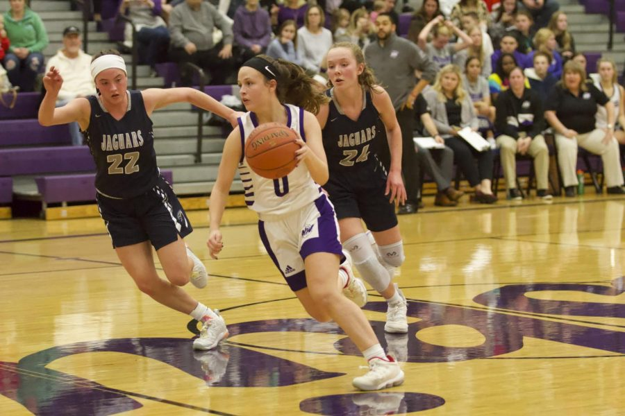 Sophomore Hayley Numrich (0) dribbles past defenders during the girls varsity basketball game against Mill Valley.