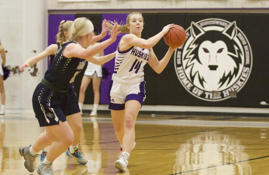 Junior Megan Edwards (14) advances the ball up the court in the girls varsity basketball game, Feb. 18.