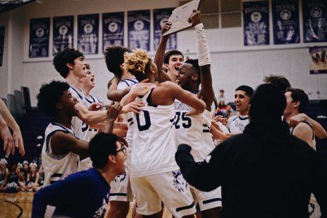 The boys basketball team celebrates their substate championship win.