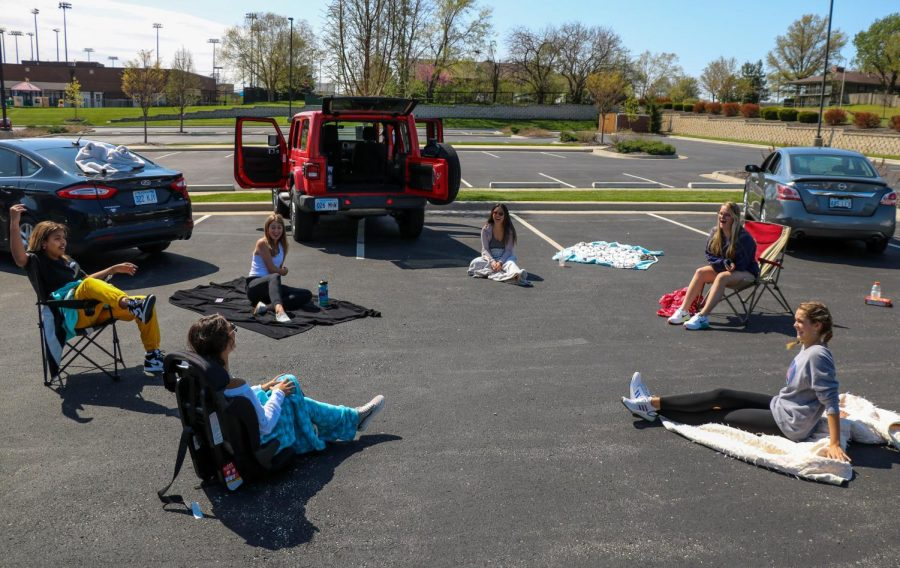 Senior Hailey Burgess sits on a blanket while at a car circle with her friends, April 15.
