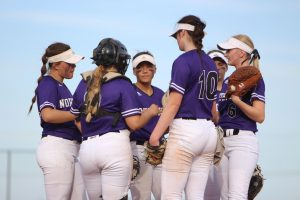 Huddled in a circle, the varsity softball team talks to each other during a game.