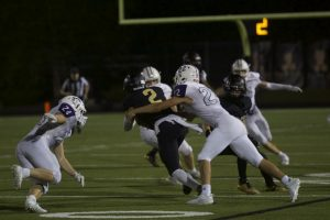 Junior Drew Kaufman tackles the Blue Valley quarterback.