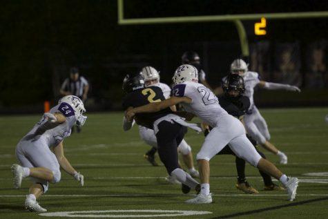 Junior Drew Kaufman tackles the Blue Valley quarterback.