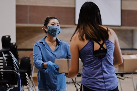 Teacher Sarah Lim hands a student a box with a mask on.