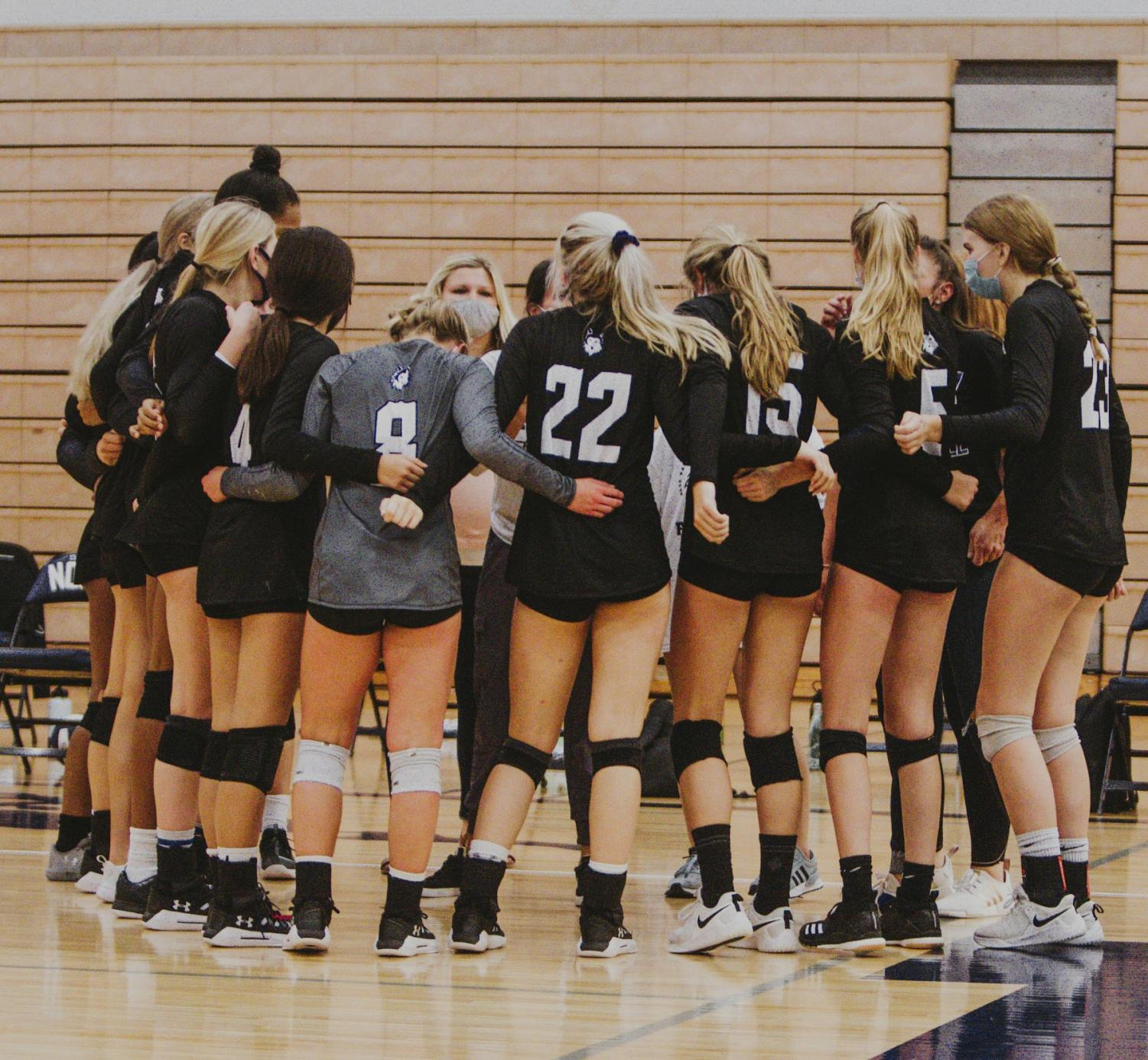 The Varsity volleyball team huddles together at the game against BVN.