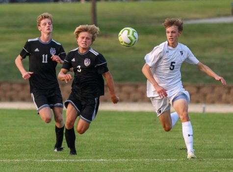 Sophomore Sam McIntosh (3) and senior Ethan Hunt (11) chase the ball in the boys varsity soccer game, Sept. 17.