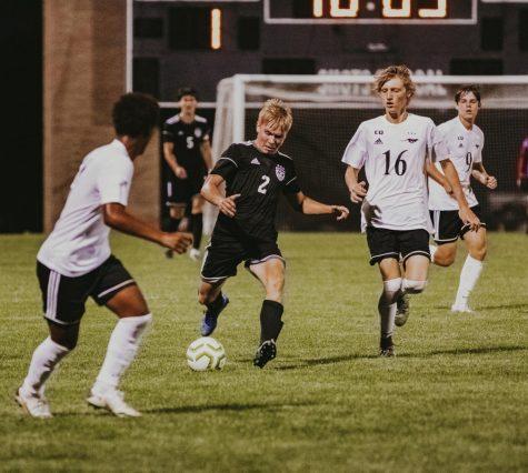 Senior Aidan Knauth dribbles the ball between two defenders in the boys varsity soccer game.
