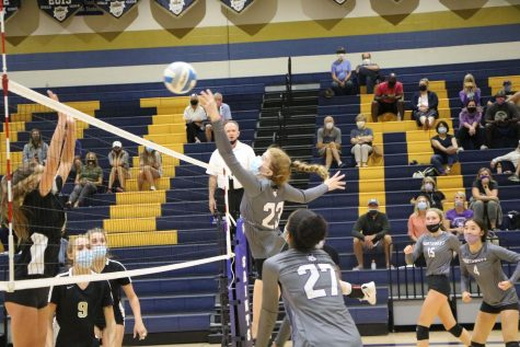 Junior Audrey Malis (23) rises to hit the ball in the girls varsity volleyball game against Blue Valley, Sept. 15.