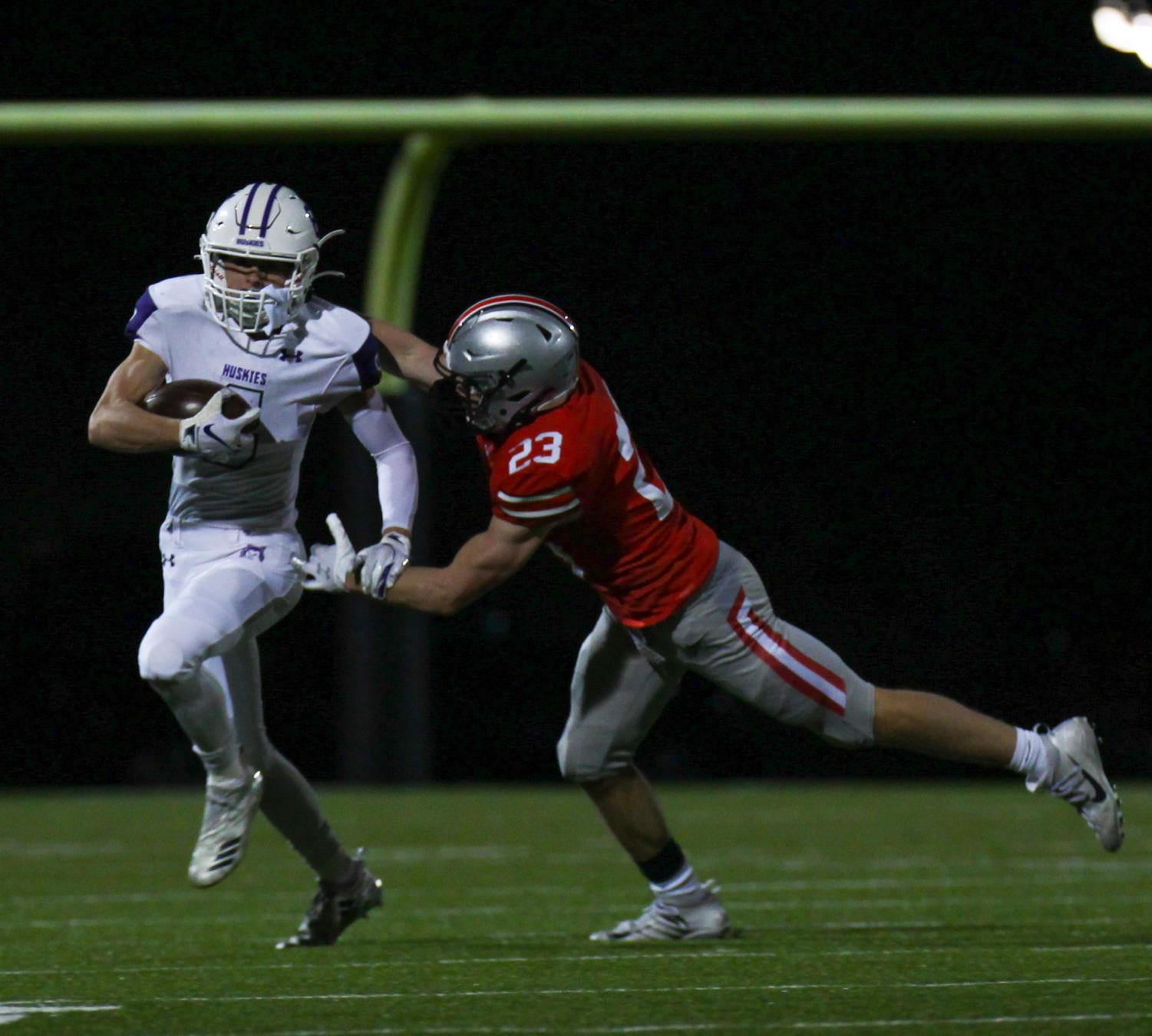 Junior Nick Cusick runs the ball in the varsity football game against Blue Valley West, Oct. 23. (Photo by Grace Davis)