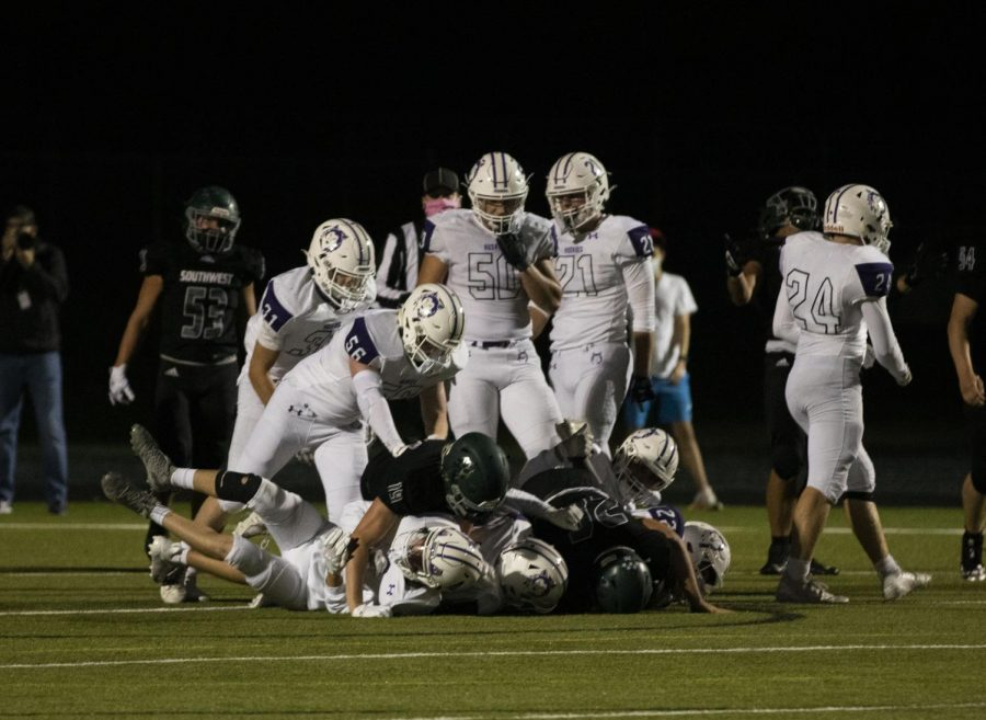 Northwest football players surround a tackle during the varsity game, Oct. 2. (Photos by Lauren Kline)