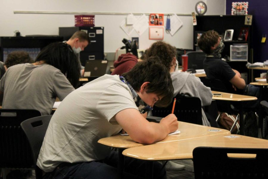 A student works on homework during class on the first day back from spring break, March 23.