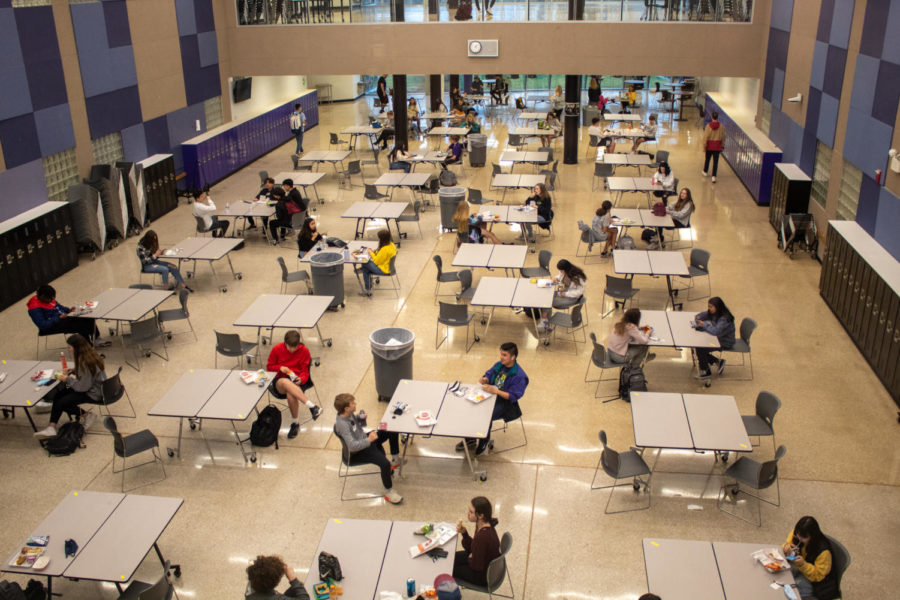 Students eat lunch in the atrium with only two students per table, March 23.