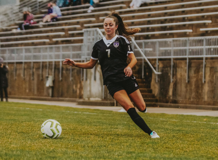 Sophomore Reagan Priest dribbles the ball in the varsity soccer game against Bishop Miege.