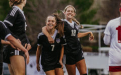 Sophomore Reagan Priest (7) celebrates scoring a goal with senior Isabel Schelhammer (18). Priest finished the game with a hat trick.