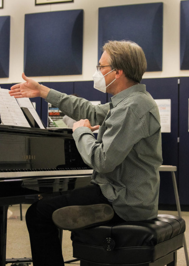 Accompanist Kurt Knecht directs the choir while playing the piano.