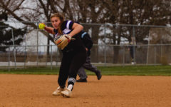 Junior Sammie Carey throws the ball to first base in the varsity softball game against St. Thomas Aquinas.