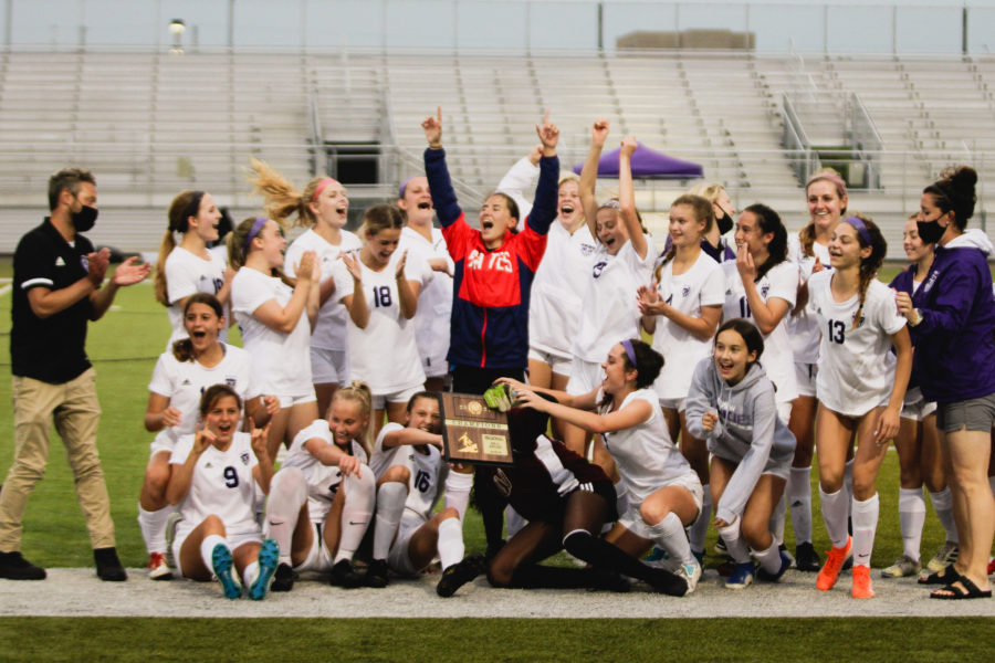 The girls varsity soccer team celebrates after receiving the regional championship trophy.