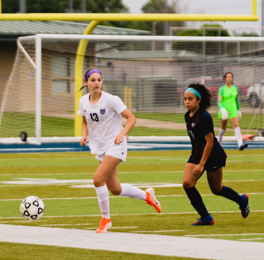 Freshman Isabelle De Buyl (13) looks for a teammate to pass to during the girls varsity soccer regional championship game.