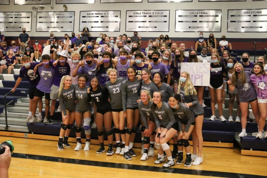The varsity volleyball team celebrates their first win of the season with the student section.