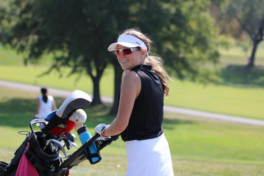 Senior Nicole Hiemenz pushes her bag during a golf practice.
