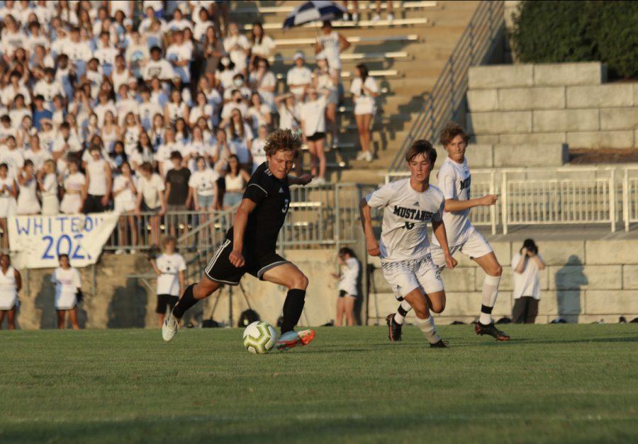Junior Sam Mcintosh prepares to kick the ball in the varsity soccer game Aug. 27.