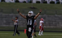 Senior quarterback Mikey Pauley celebrates scoring a touchdown during the football game against Bishop Miege High School, Sept. 10.