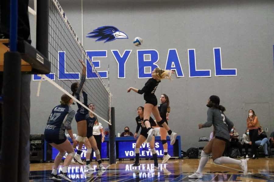 Junior Avery Ahlers spikes the ball in the match against Olathe West, Oct. 24.